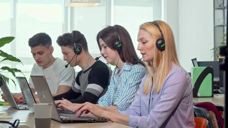 Beautiful young woman answering calls, working at customer support call center. Young people working at technical support service, wearing headsets with microphones