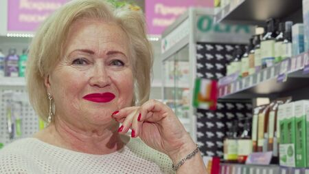 Cropped shot of elegant elderly woman shopping at drugstore. Cheerful senior lady smiling to the camera, while choosing products from the shelves of pharmacy Archivio Fotografico