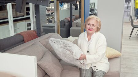 Happy senior woman choosing cushions for her living room at furniture store. Elderly female customer sitting on a couch on sale, smiling to the camera. Lifestyle, retirement concept