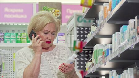 Senior woman talking on the phone while shopping at drugstore. Low angle shot of elderly female customer talking on the phone, examining products on sale at pharmacy