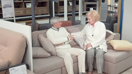 Elderly husband and wife trying new sofa, shopping for furniture. Lovely senior couple sitting on a couch at furnishings store. Elderly customers buying furniture. Retirement, home concept
