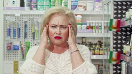 Senior woman having headache, looking for medicine at pharmacy. Elderly female customer having migraine, shopping for painkillers at the drugstore. Relief concept