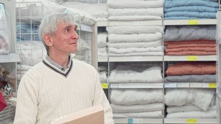 Senior man shopping for bedroom textile at furnishings store. Elderly male customer choosing bed sheets at home goods department store. Retirement, home concept