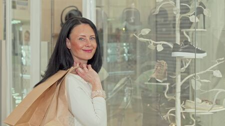 Beautiful mature woman smiling to the camera, while examining display of a store. Attractive female customer looking at the showcase of a clothing store. Fashion concept