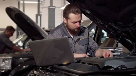 Car service worker using laptop, examining engine of a car. Bearded professional auto technician concentrating, looking under the hood of automobile. Car diagnostics concept