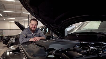 Bearded car service worker smiling to the camera, examining cars at the workshop. Cheerful auto technician enjoying working at the garage, checking engine of an automobile
