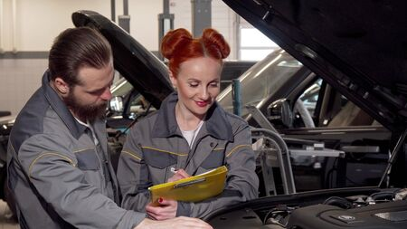 Beautiful female mechanic and her male colleague examining engine of a car. Attractive woman auto technician writing on a clipboard, looking under the hood of automobile