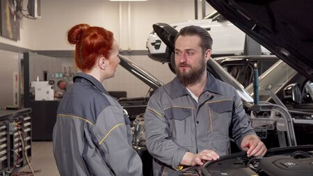 Bearded mechanic talking to his female coleague at the workshop. Two car technicians discussing work, examining car with an open hood. Female equality, occupation concept