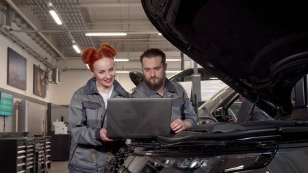Professional auto mechanics using laptop during car diagnostic at the garage. Bearded repairman talking to his female colleague, examining engine of a modern SUV at the garage