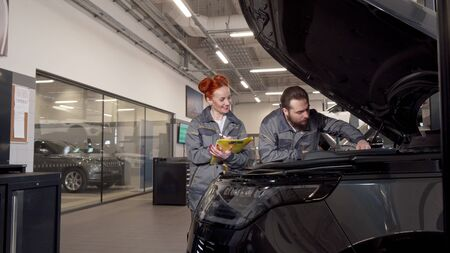 Two professional car mechanics examining engine of a car, making notes. Attractive female auto mechanic writing on a clipboard, her male colleague looking under the hood of an automobile Stock fotó