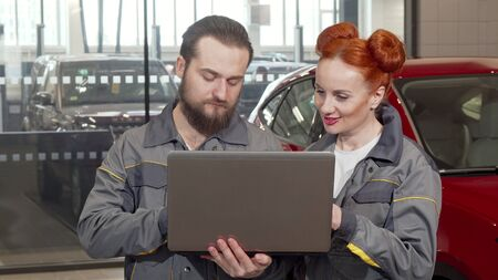 Bearded car mechanic using laptop at the garage, working with female colleague. Lovely red haired female auto technician enjoying working at the service station, talking to a co-worker