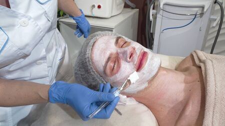 Happy man getting facial masks at beauty salon, smiling with his eyes closed. Attractive male client relaxing at spa center, beautician doing skin rejuvenating procedure. Health, relax concept
