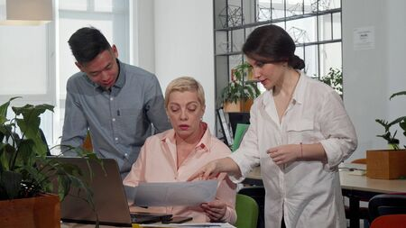 Mature female CEO talking to her workers at the meeting room. Two creative designers discussing ideas with their boss at the office. Creativity, leadership, startup concept Stock Photo