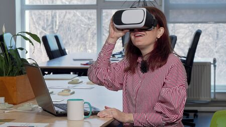 Mature businesswoman enjoying using virtual reality headset at her workplace. Cheerful female entrepreneur laughing, trying 3d vr glasses. Technology, device, gadget concept 写真素材