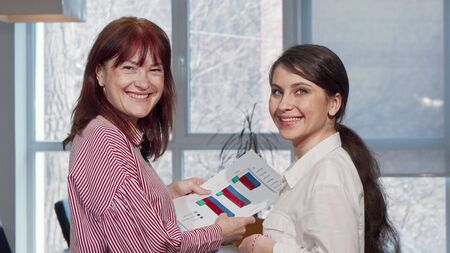 Happy businesswomen smiling to the camera, enjoying working at the office. Beautiful young businesswoman and her mature colleague examining statistic graphics. Project concept