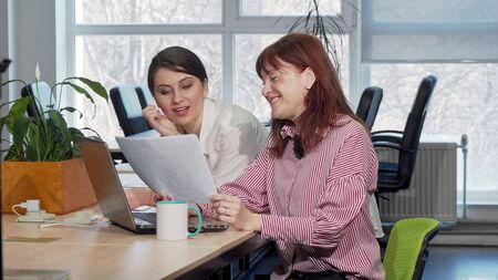 Two businesswomen doing paperwork together at the office. Lovely young female entrepreneur enjoying working with her mature colleague, examining documents. Startup concept