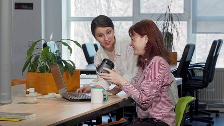 Businesswoman discussing virtual reality goggles she is using with a colleague. Young female entrepreneur talking to her co-worker about 3d vr headset. Technology, gadgets concept