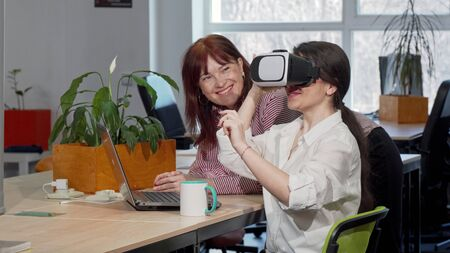 Two female business colleagues trying 3d vr glasses at work. Mature woman laughing, talking to her co-worker, while she is using virtual reality headset. Teamwork, fun concept