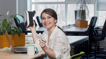 Lovely excited businesswoman laughing joyfully, using 3d virtual reality headset. Cheerful female entrepreneur enjoying trying vr goggles at work. Future, gadgets concept