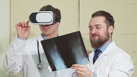 Male doctor wearing vr glasses, his colleague examining x-ray of a patient. Young practitioner using 3d virtual reality headset, working at the clinic with his assistant 写真素材