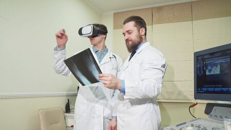 Doctor using 3d vr glasses, while his colleague examining x-ray of a patient. Two medical workers discussing x-ray of a patient, using virtual reality headset at hospital. Health, science concept Reklamní fotografie
