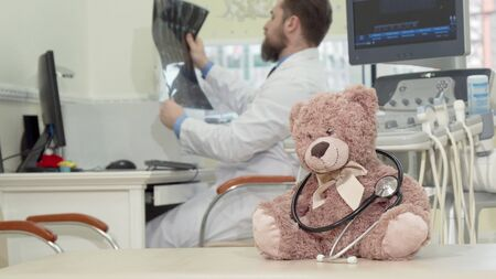Male pediatrician examining mri scan, plush toy on the foreground. Selective focus on a teddy bear with sthethoscope, male doctor working on the background. Children health concept