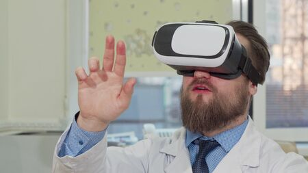 Male doctor using 3d virtual reality glasses at the hospital. Cropped shot of a bearded practitioner enjoying using vr headset at work. Medical technology, modern science concept