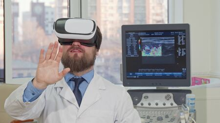 Bearded male doctor using 3d vr glasses at the hospital. Cheerful practitioner, smiling, enjoying using virtual reality headset at his clinic. Technology, science, healthcare concept 写真素材