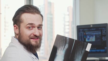 Rear view shot of a male doctor looking at foot x-ray of a patient. Cheerful bearded doctor smiling to the camera after examining x-ray at his office. Medicine, health concept