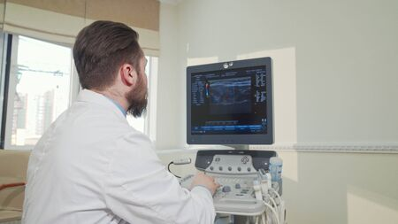 Cheerful doctor smiling to the camera, using ultrasound scanning machine. Rear view shot of a male obstetrician examining results of sonogram scanning of a patient. Health, experience concept Reklamní fotografie