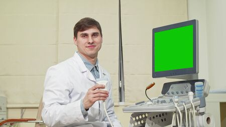 Male doctor using ultrasound scanner with chroma key screen. Happy friendly male physician smiling to the camera, operating ultrasound scanner with green screen. Medicine concept Reklamní fotografie