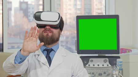 Bearded doctor wearing 3d vr glasses, computer with green chromakey screen on the back. Male physician using virtual reality headset at his clinic, copy space on green screen