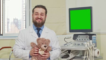 Pediatrician holding teddy bear, ultrasound scanner with green chroma key screen on the back. Doctor holding plush toy teddy bear, sitting next to ulstrasound scanner with green screen 写真素材 - 129812225