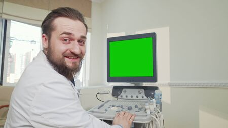 Doctor operating ultrasound scanner with green screen. Rear view shot of a male practitioner using ultrasound scanner with green mock up screen. Physician smiling to the camera