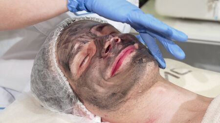 Cosmetologist preparing face of male client for carbon facial peeling. Handsome man getting skincare treatment by beautician. Man receiving facial carbon peeling