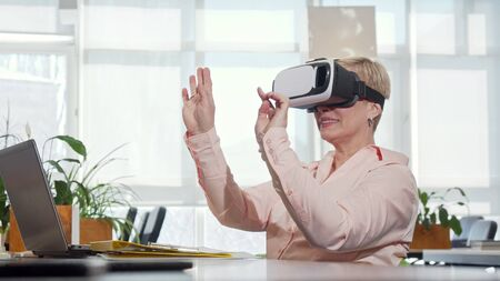 Mature businesswoman trying 3d virtual reality glasses at her workplace. Cheerful female entrepreneur wearing vr headset at the office. Interface, innovation concept