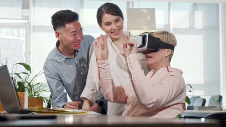 Mature businesswoman using 3d virtual reality goggles at work. Diverse business team discussing modern gadgets, female entrepreneur talking to colleagues, using vr glasses