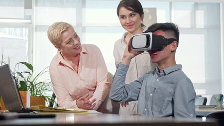 Colleagues watching businessman using 3d vr glasses. Two businesswomen talking to their co-worker while he is using virtual reality headset. Teamwork, technologies Stock Photo