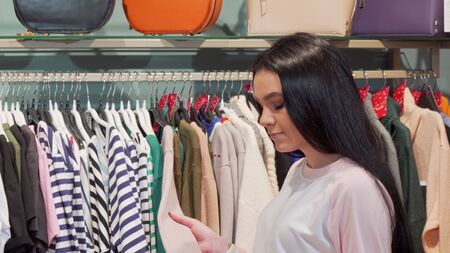 Young woman examining clothes on sale at the fashion store. Rear view shot of a female customer choosing clothes to buy. Lovely woman shopping at clothing boutique 写真素材