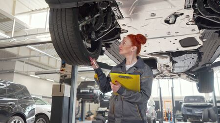 Female car mechanic walking under car on a lift, writing notes on clipboard. Low angle shot of a woman auto technician examining lifted automobile. Profession, occupation concept 스톡 콘텐츠