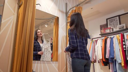 Low angle shot of a beautiful young woman trying a dress at clothing store. Attractive female customer enjoying shopping for new clothes, choosing a dress. Consumerism concept 写真素材