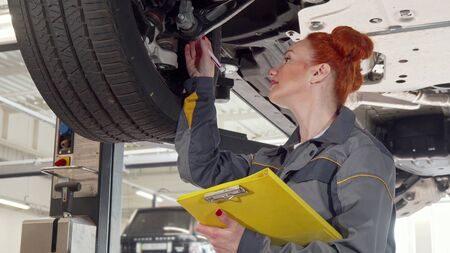Female car mechanic examining wheels of a car on a lift, taking notes on clipboard. Lovely woman auto technician working at her service station. Female equality, professions concept