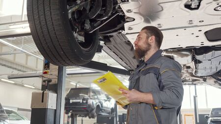 Low angle shot of a car mechanic taking notes, examining lifted auto. Professional automobile technician filling papers on auto diagnostics. Insurance, repairworks concept