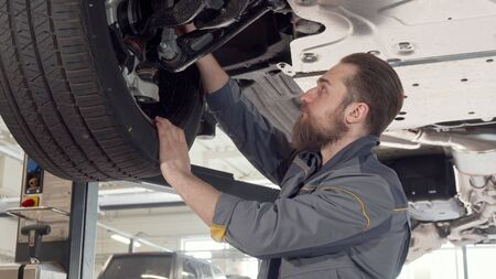 Bearded male mechanic checking wheels of a car on a lift at the garage. Professional auto technician working with lifted car, examining wheels. Safety, insurance, maintenance concept Stock fotó