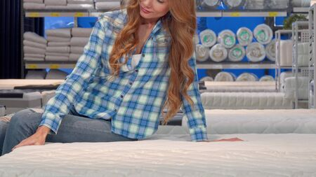 Red haired woman smiling, sitting on a new orthopedic mattress at the store. Cropped shot of a female customer examining comfortable beds at furnishings shop. Sleep, relax concept