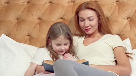Lovely little girl and her beautiful mom smiling to the camera, reading a book. Attractive woman hugging her little daughter, lying in bed, enjoying reading fairytale