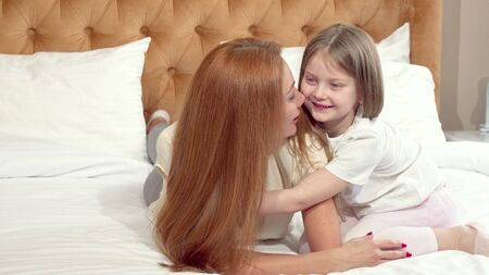 Cute little girl enjoying resting at home with her mother. Adorable little girl whispering to her mothers ear. Beautiful woman rubbing noses with her cute daughter. Children, kids concept Imagens