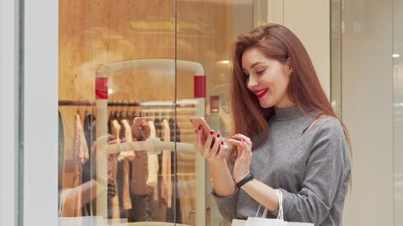 Lovely young woman laughing, using smart phone while shopping at the mall. Attractive female shopper holding shopping bags, typing messages on her phone. Sales, social media concept Stock fotó