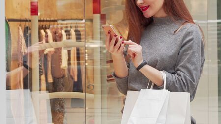 Woman smiling, browsing on her smart phone while shopping at the mall. Cropped shot of a cheerful female shopper holding shopping bags, using phone. Online, retail concept