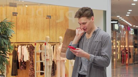 Young man smiling, using smart phone while shopping at the mall. Cheerful male shopper browsing online on his phone, holding shopping bags, copy space. Retail concept